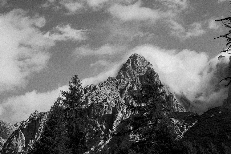 Black and white of mountain and tree tops with clouds in Dolomites, Italy.