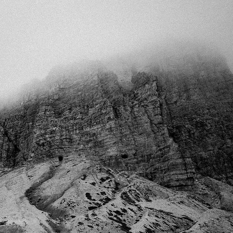 Black and white grainy view of misty mountains, Dolomites, Italy.
