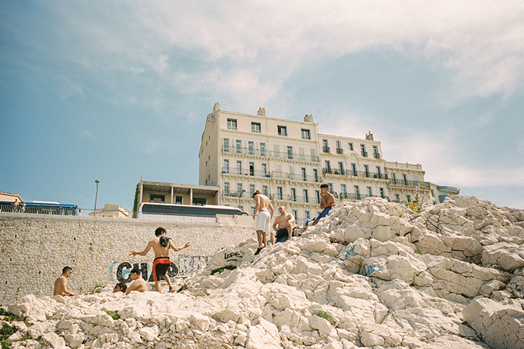Colour 35mm film of 7 local boys sitting on rocks enjoying sun and building in background, Marseille France.