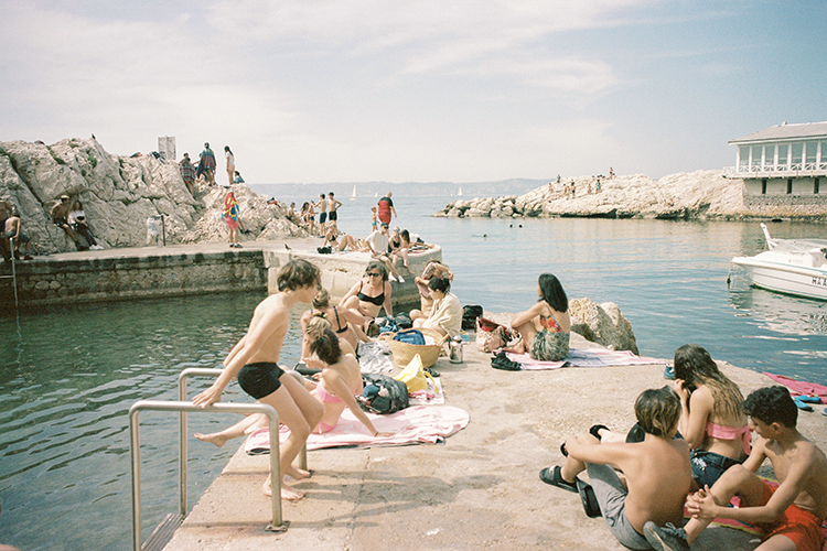 Colour 35mm small harbour scene of people sitting on the concrete sunning and a boy getting out of the water on the left, people on rocks and the mediterranean behind.