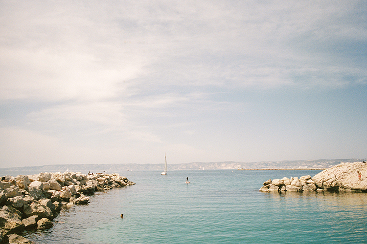 Colour 35mm frame of little harbour in Marseille France with Mediterranean and small sail boat in the background.